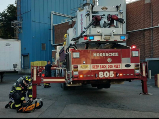 Firefighter with saw next to fire truck